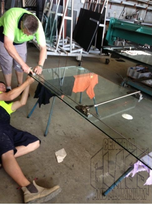 Lying On The Floor Attaching Panic Bars For New Frameless Glass Doors At Gold Coast Turf Club